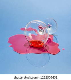 A glass and spilled liquor on a light blue background. Art photo.