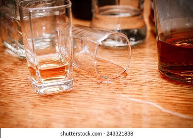 Glass, spilled whiskey and empty bottles on the bar. Abuse of alcohol hangover. Alcoholism concept. Drunk driver concept