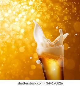 glass of splashing beer against golden bokeh background