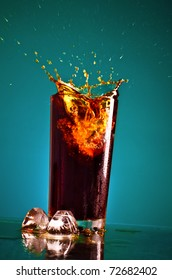 glass with splashing cola on blue background