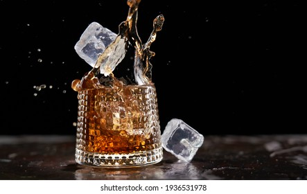Glass of splashing whiskey with icecube on stone table, on black background. Whiskey splash concept, copy space for text.