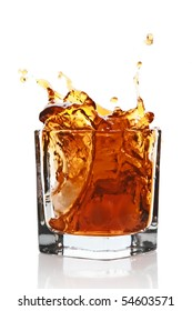 Glass with splashing whisky drink. Isolated on a white background