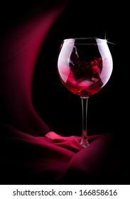 glass of splashing wine with red silk on black background