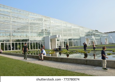Glass and steel building exterior with people relaxing by a pool, Botanical garden of Padua, Italy, Orto Botanico di Padova, Italia