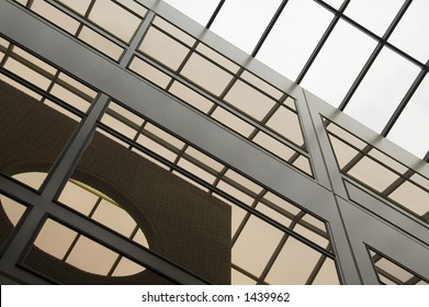 Glass and steel reflecting skylight and brick wall in atrium of college building