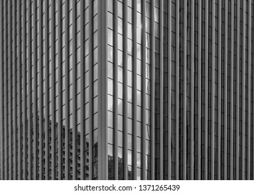 Glass and Steel Skyscraper Corner.  Black and white study of a reflective glass building with clouds and sky reflected.