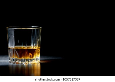 a glass of straight whiskey on a dark wooden background, whisky