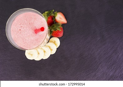 Glass of strawberry and banana smoothie, isolated on slate plate. Top view.