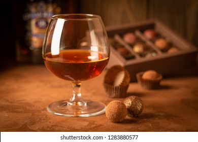 A glass of strong alcoholic drink brandy or brandy and a box of chocolates on a dark background. Selective focus.