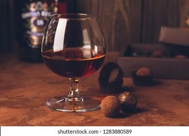 A glass of strong alcoholic drink brandy or brandy and a box of chocolates on a dark background. Copy space.