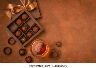 A glass of strong alcoholic drink brandy or brandy and a box of chocolates on a dark background. Flat layout.