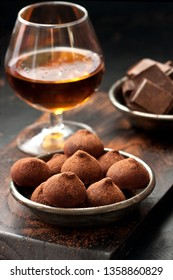 Glass of strong alcoholic drink brandy or whiskey  and truffles candy made of  chocolate on  dark background