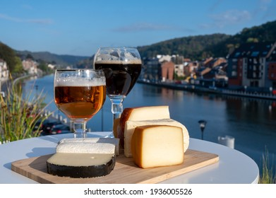 Glass of strong Belgian abbey beer and tasting of cheeses made with trappist beer and fine herbs with view on Maas river in Dinant, Wallonia, Belgium