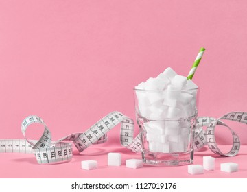 Glass with sugar cubes and measuring tape. Weight control diet concept