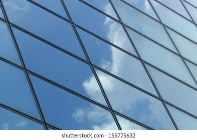 glass surface of a building with reflection of clouds and sky in it