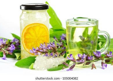 Glass of sweet herbal tea with flowering salvia , sugar crystals and sliced orange, a medicinal remedy used in Auyurveda naturopathy