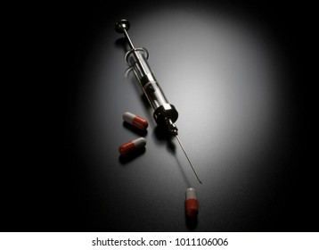 Glass syringe and with tablets of medicine. Pills and needles. Lethal drugs, narcotics and addiction.