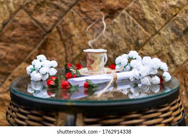 Glass Table With Fresh Coffee Steaming Romantic Flowers And Vintage Letter