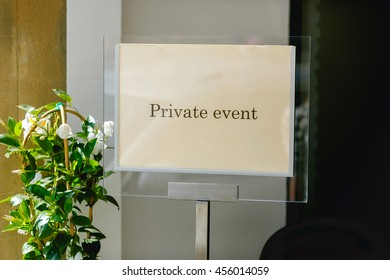 Glass table with lettering 'Private event' stands behind the door