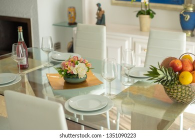 glass table setting with flower arrangement and fruit