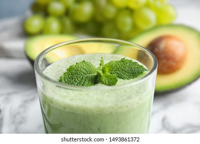 Glass of tasty avocado smoothie with mint on table, closeup