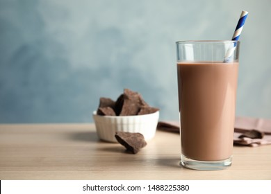 Glass of tasty chocolate milk on wooden table, space for text. Dairy drink