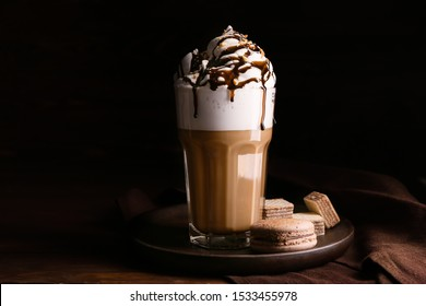 Glass of tasty frappe coffee with sweets on wooden table