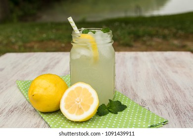 Glass of tasty lemonade with lemons and mint sprigs outside by the lake in summer