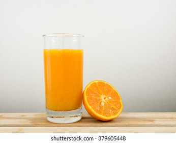 The glass of tasty pure orange juice and fresh orange half on wooden tray for a good healthy.