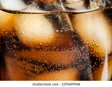 Glass of tasty refreshing cola with ice cubes on black background, closeup