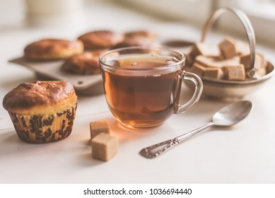 A glass of tea and freshly baked muffins on the table - natural light