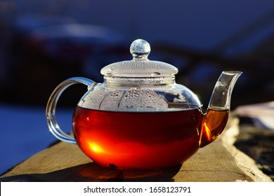 Glass teapot with black tea. The sun is reflected in the teapot. Boiling water, hot tea. Drops on a glass teapot. Tea on the street in the village.