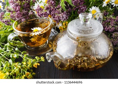 Glass teapot and cup with green tea on old wooden table with fresh herbs