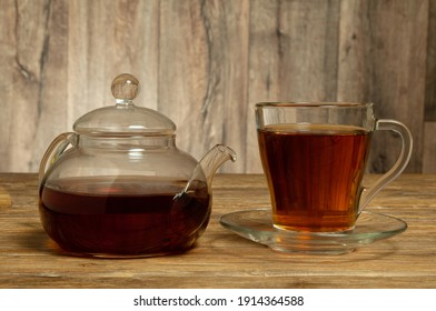 Glass teapot and glass cup with saucer with tea on wooden table