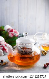Glass teapot with flowers tied tea, Hot tea in glass teapot and honey with metal honey stick on stone background, Christmas concept