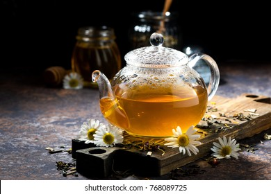 glass teapot of fragrant chamomile tea on dark background, closeup