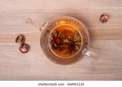 A glass teapot with Lotus Flower Chinese tea on wooden background.