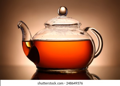 Glass teapot on brown background