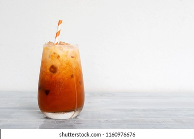 glass of Thai iced tea with milk on wooden table