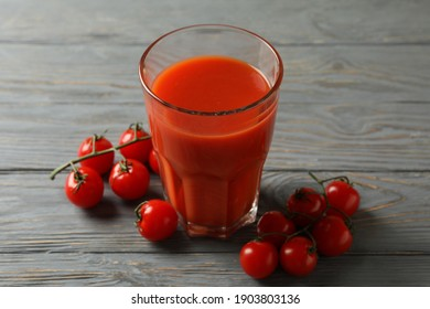 Glass of tomato juice and tomatoes on gray wooden table