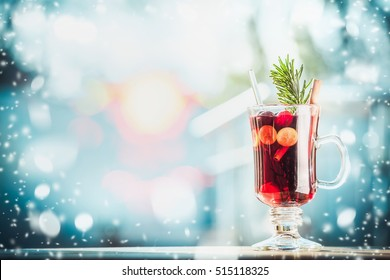 Glass of  traditional mulled wine or punch on table at  frosty winter day background with snow