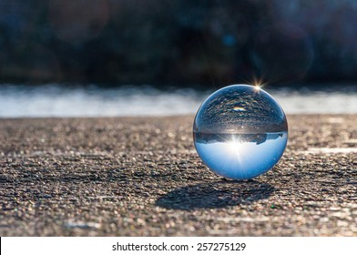 Glass transparent ball on dark background and grainy surface. Texture, outdoors