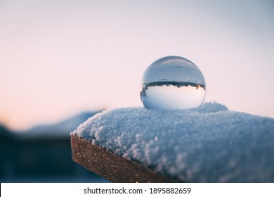 glass transparent ball in the snow in winter, sun rays reflection. severe frost, cold