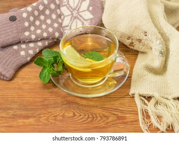 Glass transparent cup of tea with lemon slice and mint leaf on a saucer with mint twig on a rustic wooden table beside of the women's woolen mittens and knitted scarf