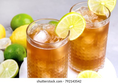 Glass of Tsasty Ice Tea with Ice Cubes and Citrus Cold Summ er Beverage Wooden Squeezer and Raw Lemons and Limes on Background Close Up