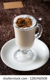 Glass of Turkish milky hot drink sahlep or salep on textured vintage brown background.