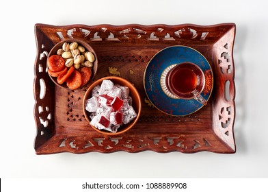 Glass of Turkish red tea with traditional eastern sweets rahat lokum, pistachios and dried apricots on wooden tray. Breakfast concept on white background, top view
