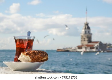 A glass of Turkish tea and bagel against Maidens Tower on sea in Istanbul, Turkey