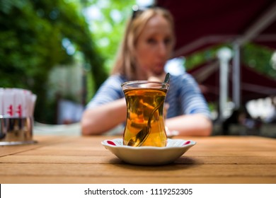 A glass of Turkish tea with girl in background