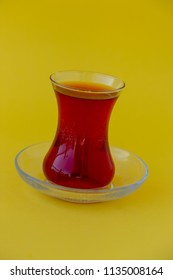 Glass of Turkish tea on yellow background